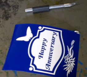 Cutting out a design from the stencil sheet for the sandblasted wine bottle.
