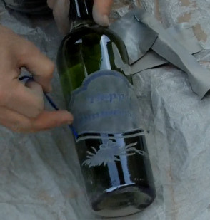 Finishing the sandblasted wine bottle by removing the stencil.