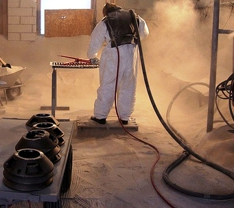 Picture of a man using sandblaster rental equipment.
